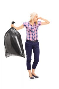 woman holding nose with smelly trash bag